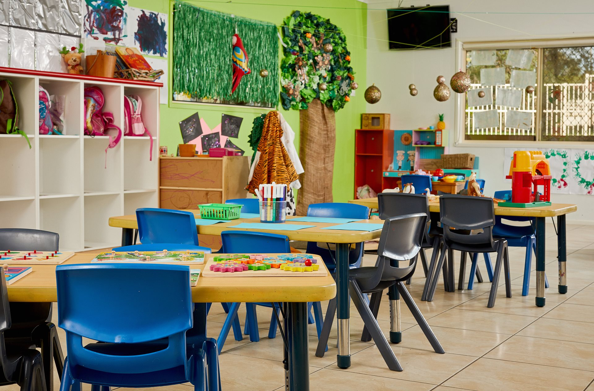Classroom with tables and chairs and childrens art hanging from walls
