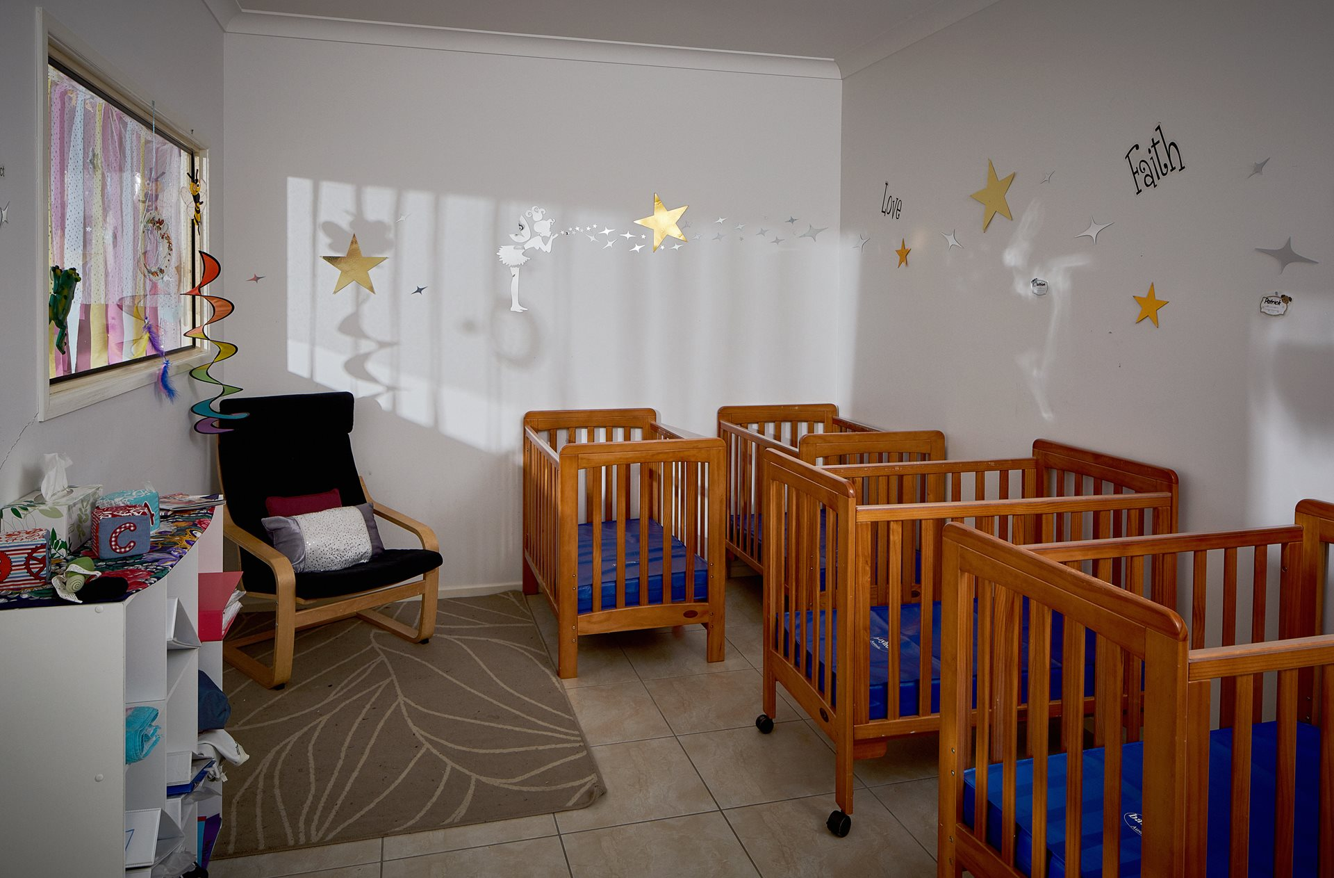 A nursery room with 4 baby cots and rocking chair in view