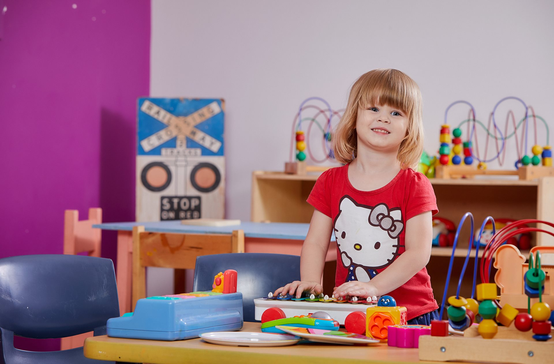 Smiling child in classroom playing with toys on table