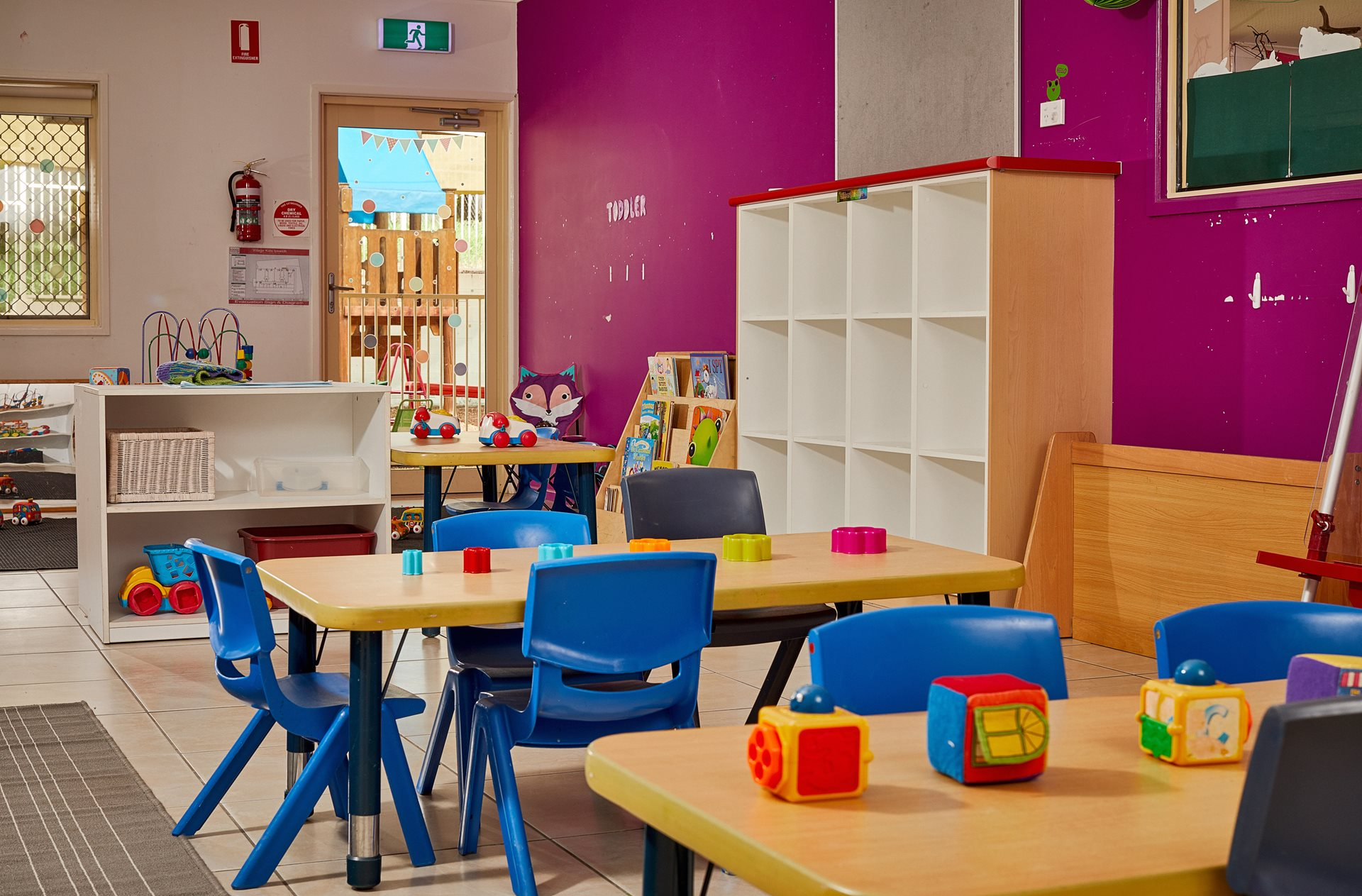 Toddler classroom with tables and chairs with toys on tables